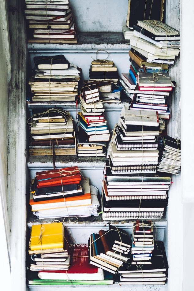 book stack on stairs many notebooks